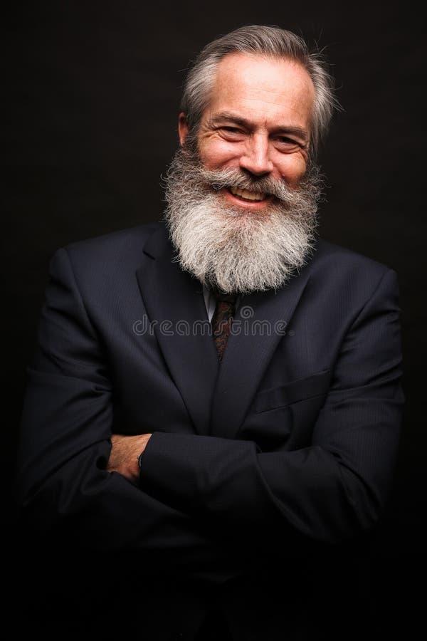 Bärande dräkt för mogen manlig modell med den gråa frisyren och skägget arkivfoto
