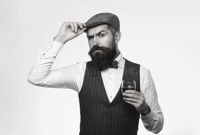 Bärande dräkt för skäggig man och drickawhisky, konjak, konjak Uppsökt och exponeringsglas av whisky Sommelieren smakar dyrt arkivfoton