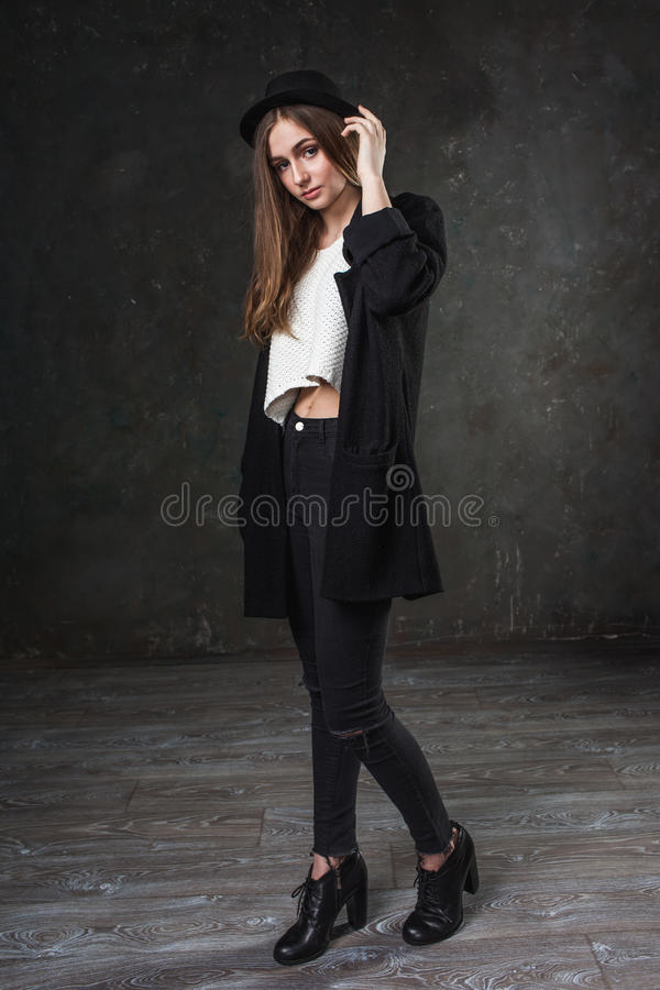 Bärande dräkt- och svartklassikerhatt för glad nätt flicka arkivfoto