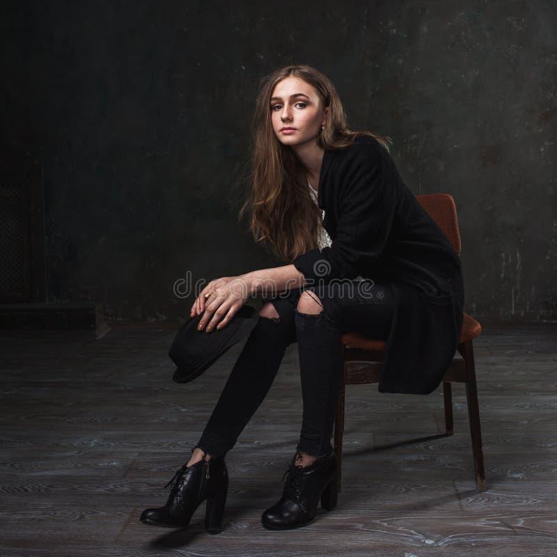 Bärande dräkt- och svartklassikerhatt för glad nätt flicka royaltyfria foton