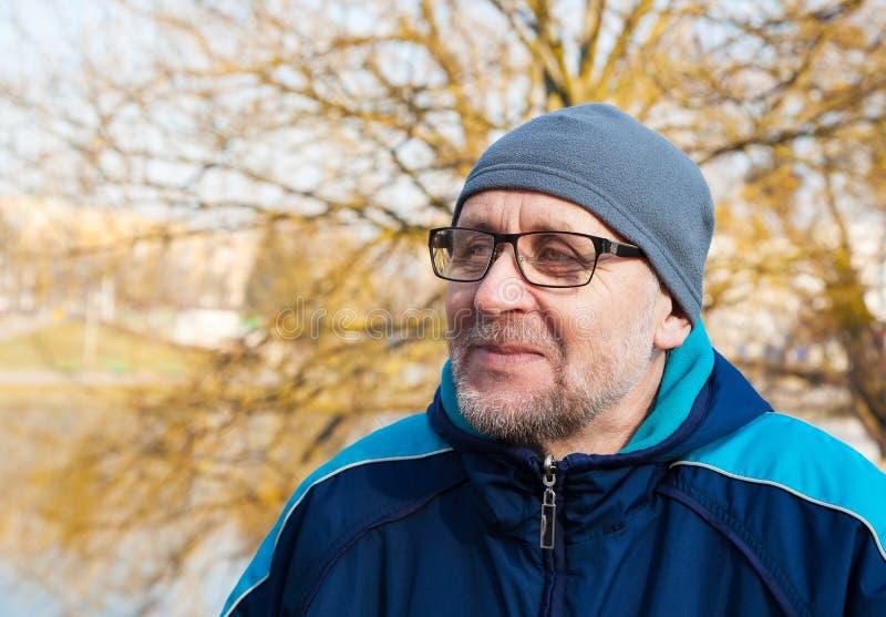 Bärande exponeringsglas för äldre man, en grå hatt och blått omslag i en cit royaltyfri fotografi