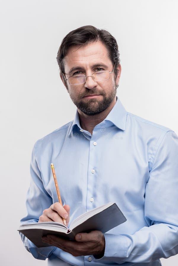 Bärande exponeringsglas för allvarlig skäggig mogen man som rymmer blyertspennadanandeanmärkningar royaltyfri bild