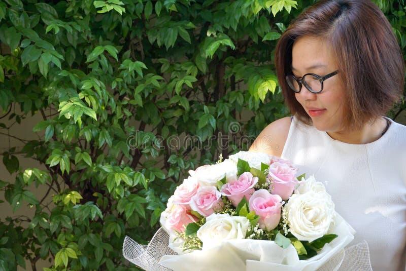 Bärande exponeringsglas för asiatisk dam som ler och rymmer den härliga buketten royaltyfri foto