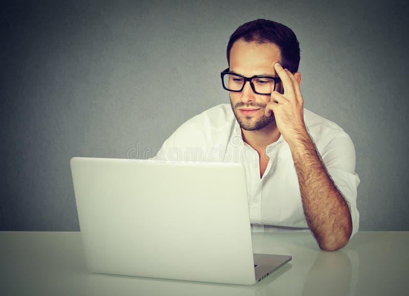 Bärande exponeringsglas för eftertänksam affärsman som sitter på skrivbordet som arbetar på hans bärbar dator royaltyfri foto