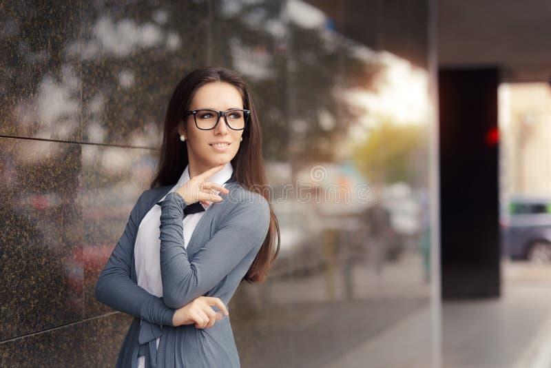 Bärande exponeringsglas för elegant kvinna som står ut i staden royaltyfri foto
