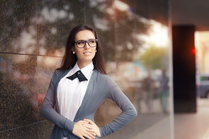 Bärande exponeringsglas för elegant kvinna som står ut i staden arkivfoto