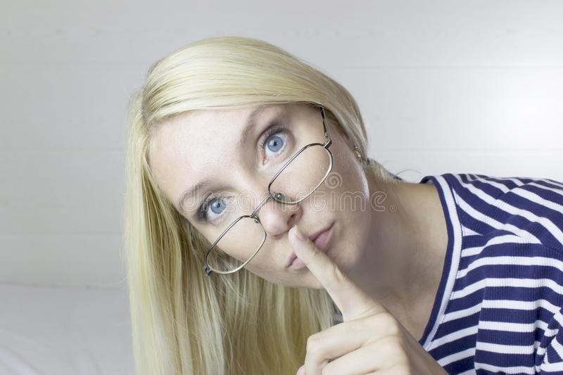 Bärande exponeringsglas för emotionell härlig gullig blond kvinna, ljus - grå bakgrund Ansiktsuttryck av tystnad royaltyfria foton