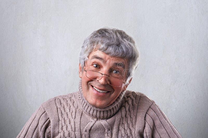 Bärande exponeringsglas för en positiv gladlynt för sort som mogen man vänligen ser in i kameran som har försiktigt leende Le den arkivfoto