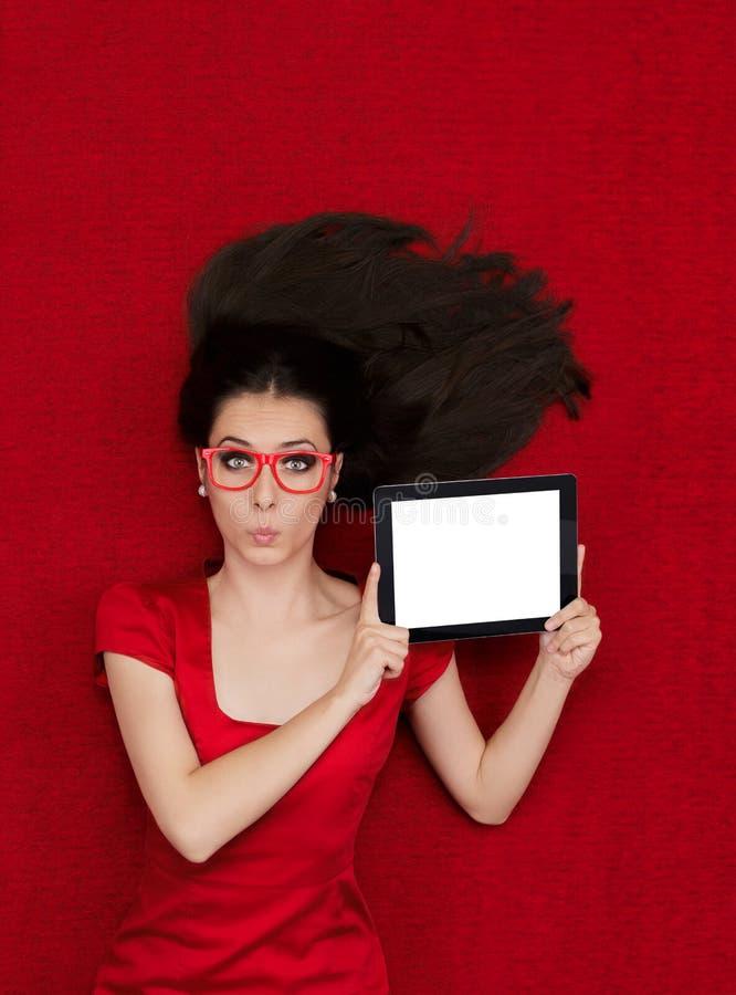 Bärande exponeringsglas för förvånad kvinna som rymmer minnestavlan fotografering för bildbyråer