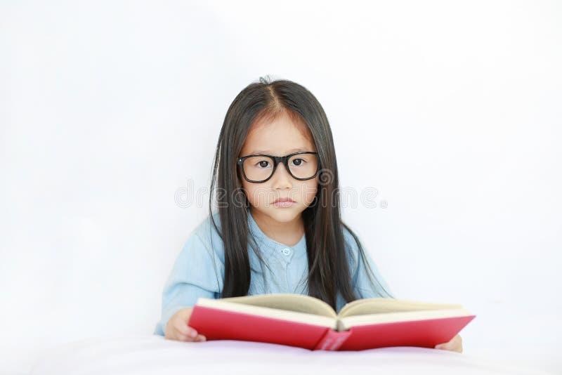 Bärande exponeringsglas för gullig liten asiatisk barnflicka som läser hardcoverboken som ligger på säng mot vit bakgrund arkivbilder