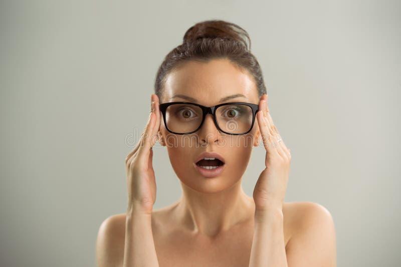 Bärande exponeringsglas för kvinna och se förvånat royaltyfri foto