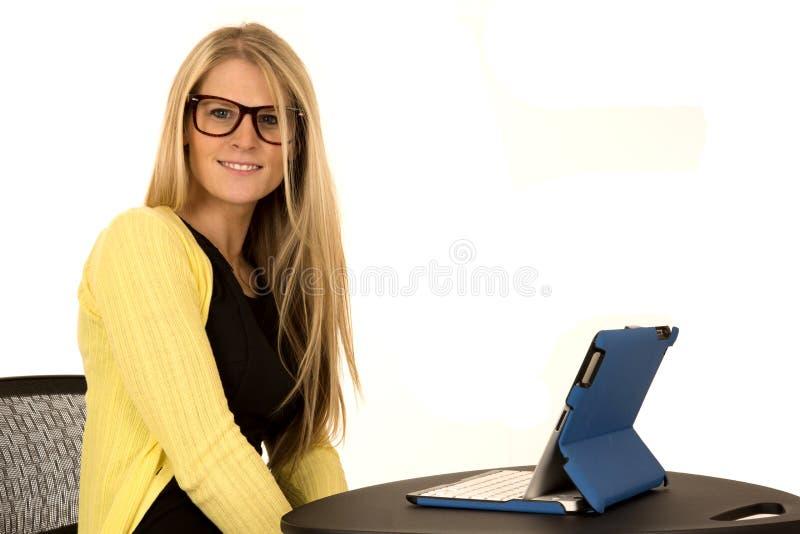 Bärande exponeringsglas för nätt ung blondin som sitter på skrivbordet royaltyfri foto