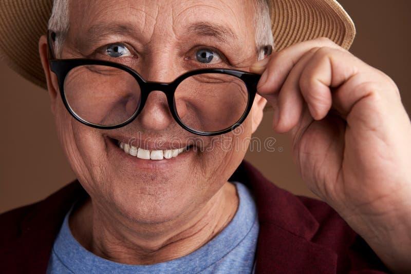 Bärande exponeringsglas för positiv man och le, medan trycka på dem royaltyfri foto