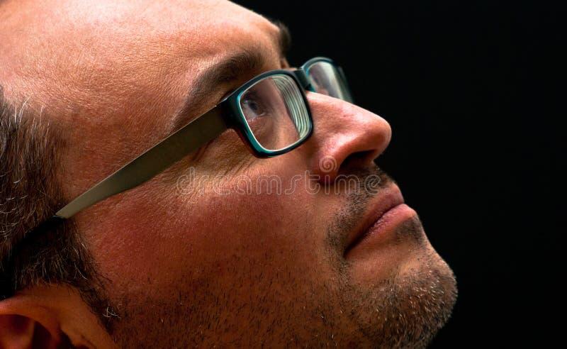 Bärande exponeringsglas för skäggig caucasian man som ser upp på svart arkivbilder