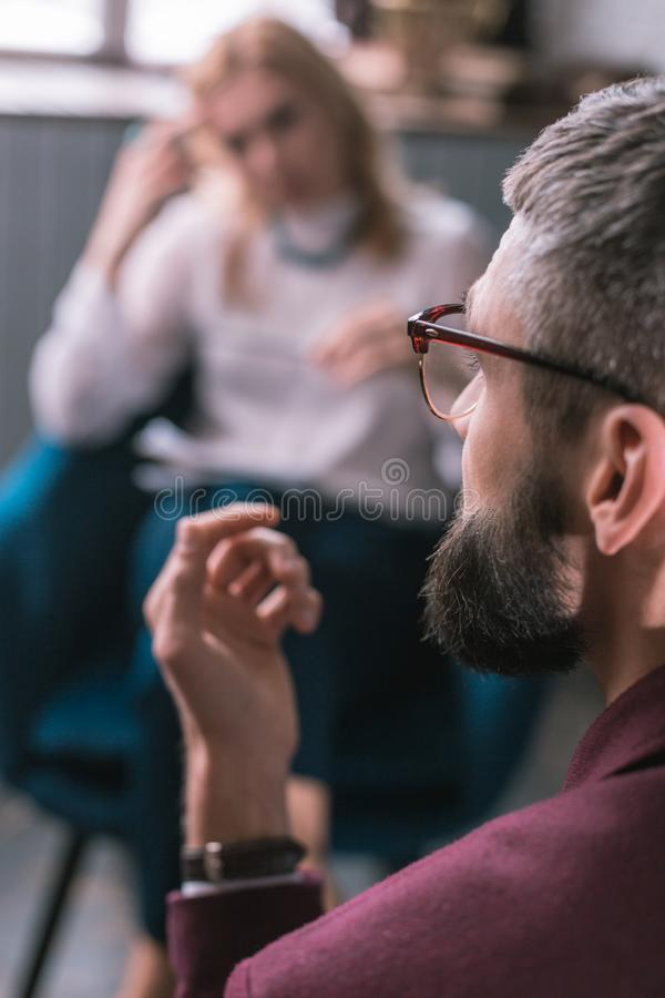 Bärande exponeringsglas för skäggig mörker-haired affärsman som besöker psykologen royaltyfri bild