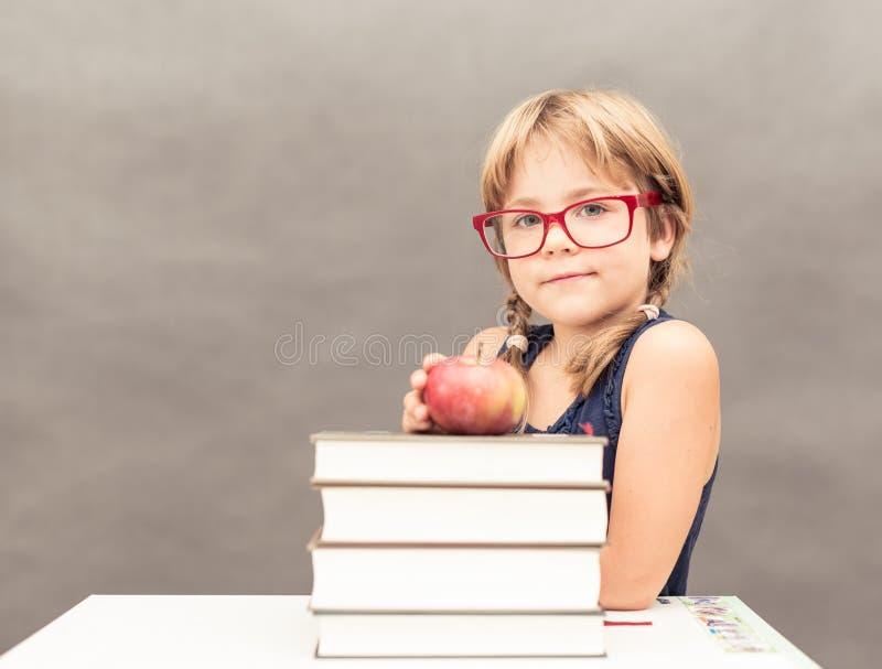 Bärande exponeringsglas för skolflicka som sitter på en tabell med en bunt av th arkivbilder