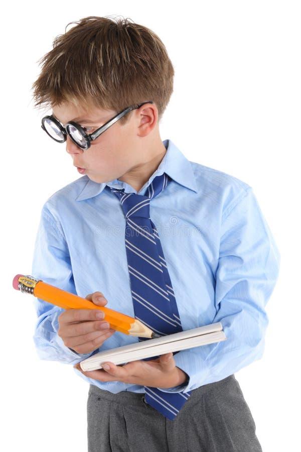 Bärande exponeringsglas för skolpojke som rymmer boken och blyertspennan och ser si royaltyfri fotografi