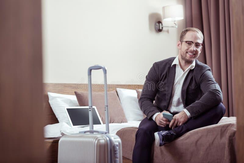 Bärande exponeringsglas för stilfull man som sitter på säng i hotellrum medan på affärstur arkivfoton
