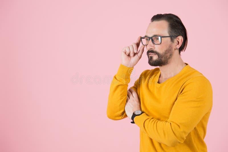 Bärande exponeringsglas för stilig freelancer som ser av till rätten av ramen Man med exponeringsglas som söker analytiskt uttryc arkivfoto