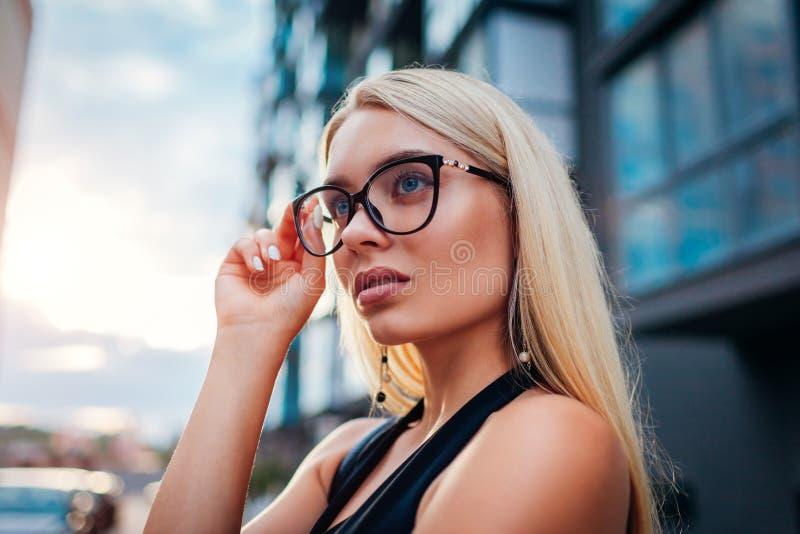 Bärande exponeringsglas för ung blond affärskvinna vid affärsmitten i stad guld- modell för klänningmode Formell stil arkivbilder