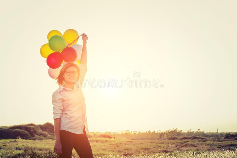 Bärande exponeringsglas för ung härlig kvinna som rymmer ballonger i fien arkivfoto