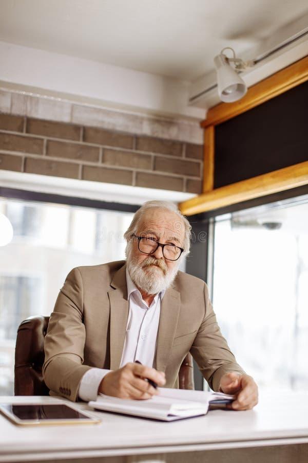 Bärande exponeringsglas för upptagen eftertänksam gammal man och utgöra nytt affärsplan arkivbilder