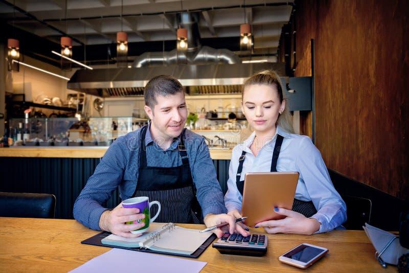 Bärande förkläde för man som och för kvinna gör räkenskap efter timmar i en liten restaurang Anställda som kontrollerar månatliga royaltyfria bilder