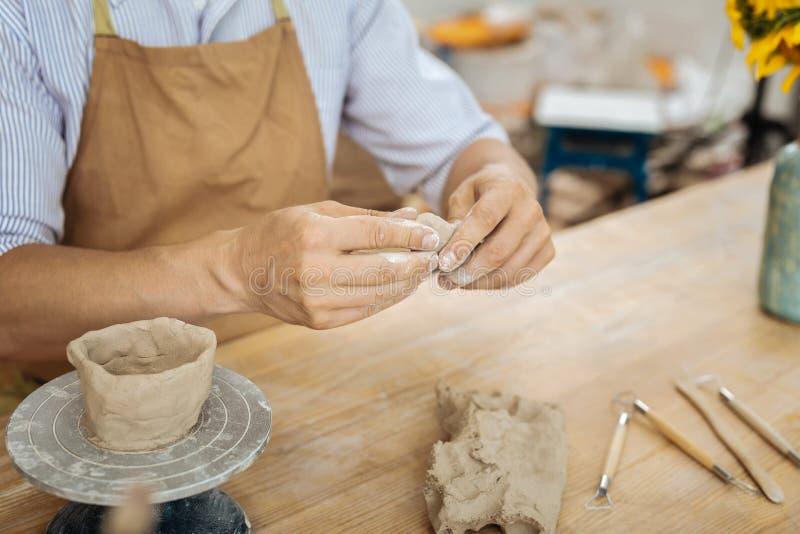 Bärande förklädesammanträde för Ceramist på tabellen som bildar små objekt royaltyfri bild
