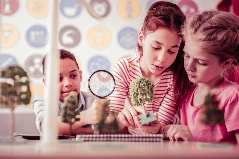 Bärande förstoringsglas för nyfiken liten student med en hand arkivfoto