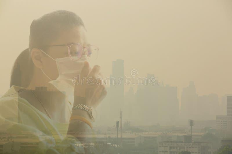 Bärande framsidamaskering för kvinna på grund av luftförorening i Bangkok royaltyfri bild