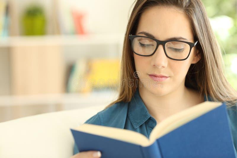 Bärande glasögon för allvarlig kvinna som läser en pappers- bok arkivbild