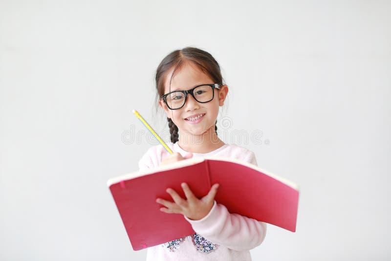 Bärande glasögon för lycklig liten asiatisk barnflicka och att rymma en bok och att skriva med blyertspennan på vit bakgrund fotografering för bildbyråer