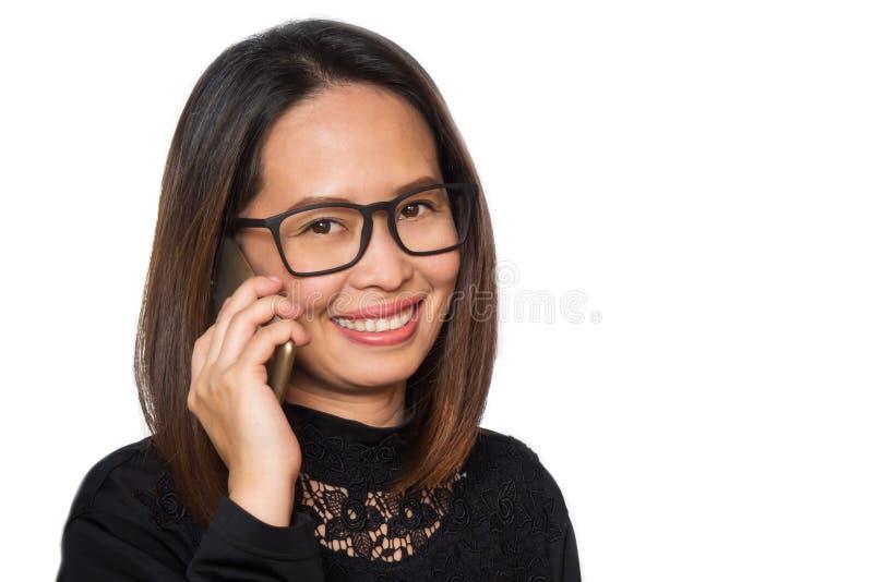 Bärande glasögon för mellersta vuxen asiatisk kvinna genom att använda den smarta telefonen S royaltyfria bilder