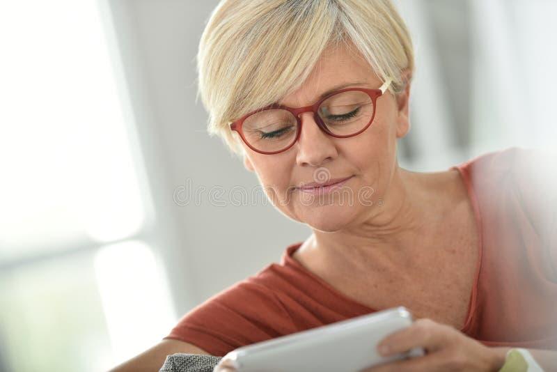 Bärande glasögon för moderiktig hög kvinna och användasmartphone royaltyfri foto