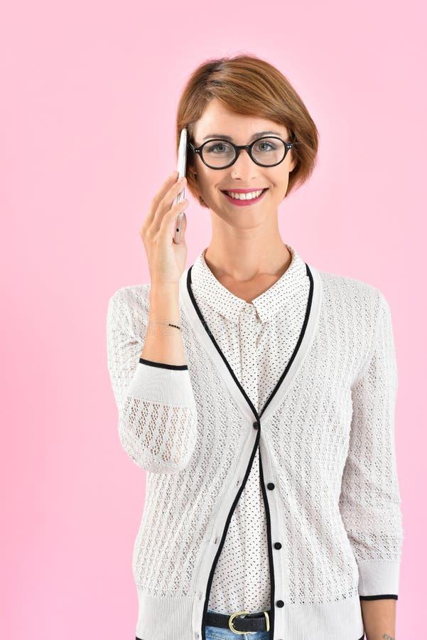 Bärande glasögon för moderiktig kvinna och samtal på smartphonen fotografering för bildbyråer