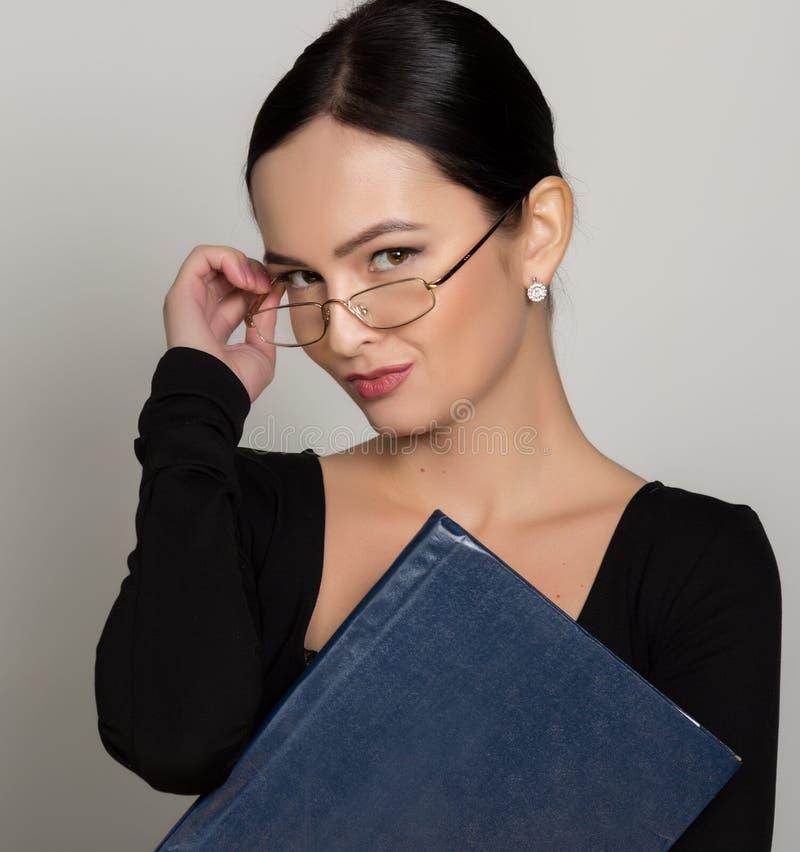 Bärande glasögon för ung härlig asiatisk affärskvinna med mappen för legitimationshandlingar royaltyfria bilder