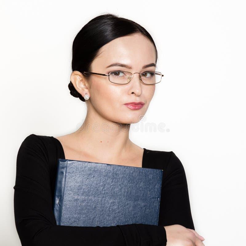 Bärande glasögon för ung härlig asiatisk affärskvinna med mappen för legitimationshandlingar arkivbild