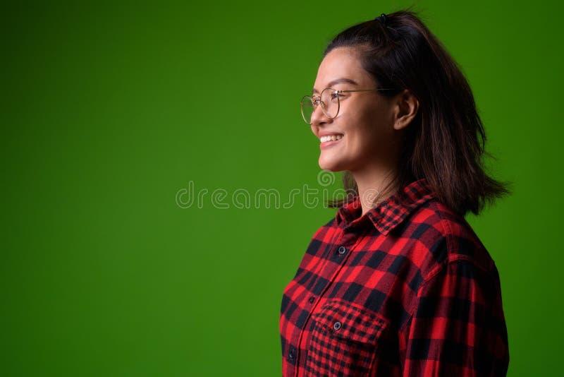Bärande glasögon för ung härlig asiatisk hipsterkvinna och röd rutig skjorta royaltyfri fotografi
