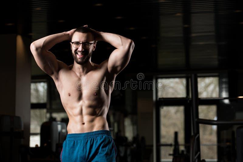 Bärande glasögon för ung kroppsbyggare som böjer muskler royaltyfria bilder