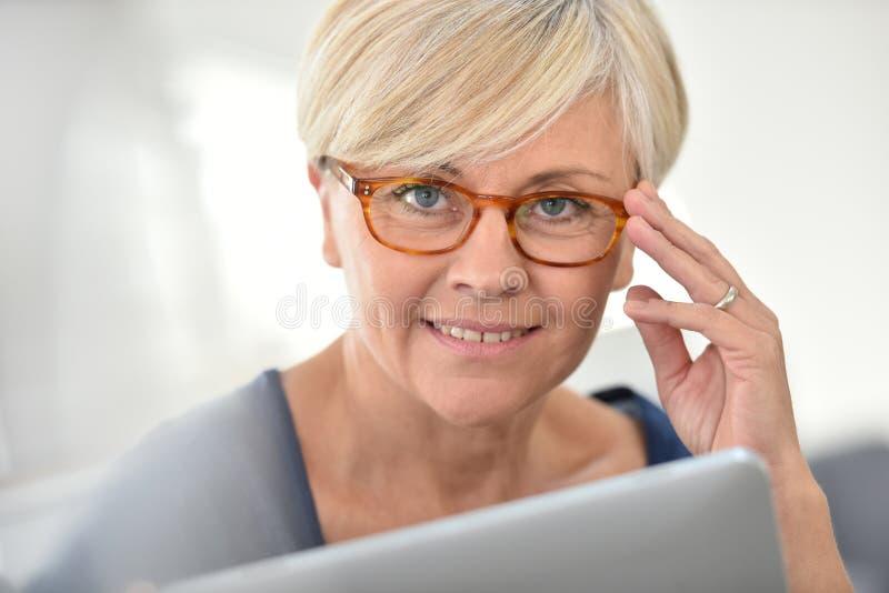 Bärande glasögon för utsmyckad hög kvinna royaltyfri fotografi