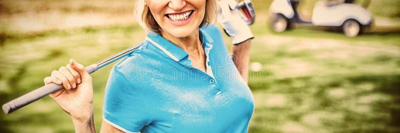 Bärande golfklubb för lycklig mogen kvinna arkivbilder