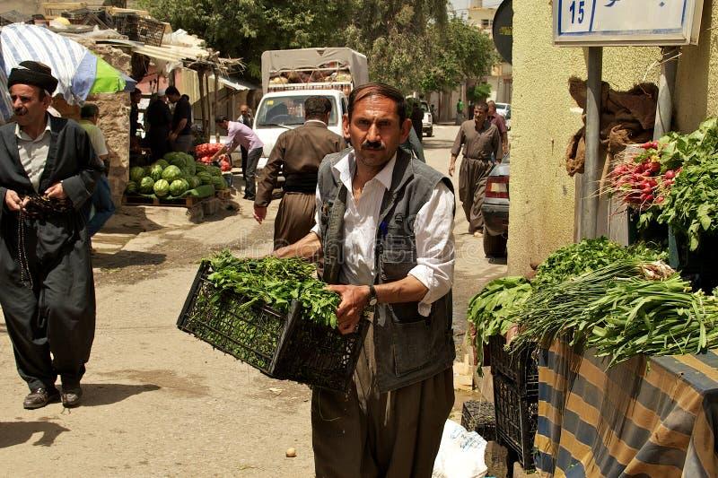Bärande grönsaker för specerihandlare till hans ställning på basaren (marknad) i Irak fotografering för bildbyråer