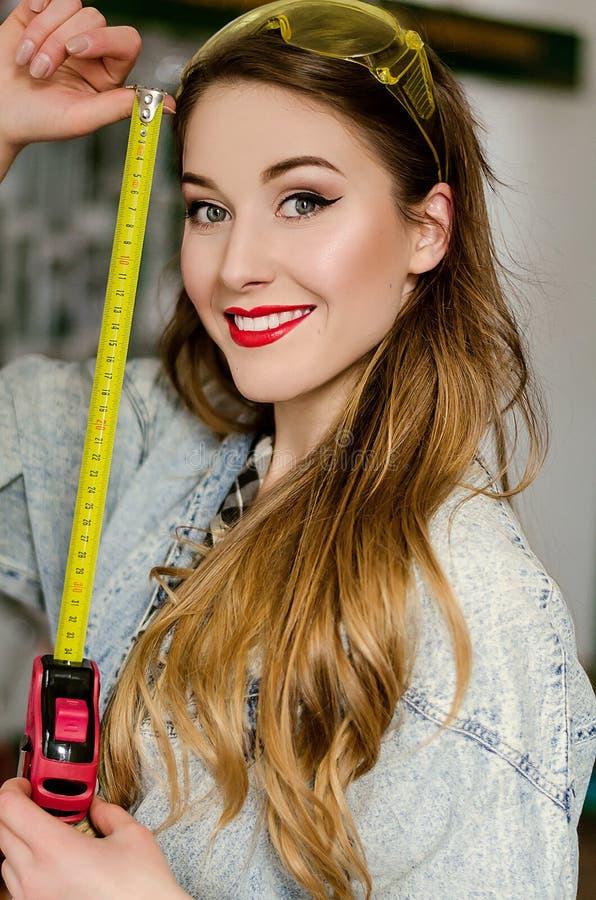 Bärande grov bomullstvilljumpsuit och exponeringsglas för ung kvinna med det långa hårinnehavet, i måttband och att le för händer royaltyfri fotografi