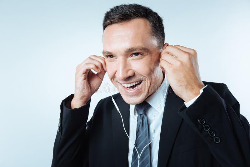 Bärande hörlurar för gladlynt affärsman arkivbild