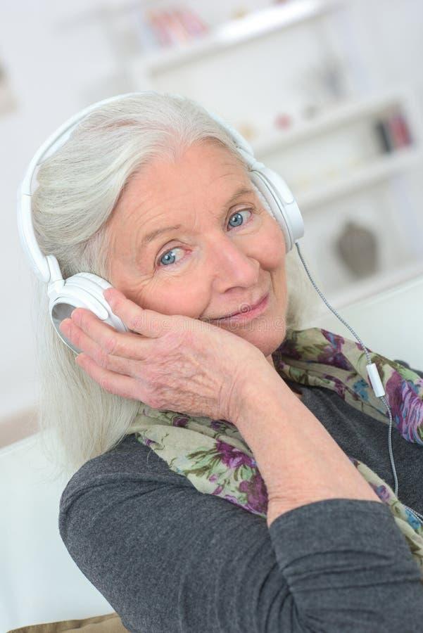 Bärande hörlurar för hög dam royaltyfri fotografi