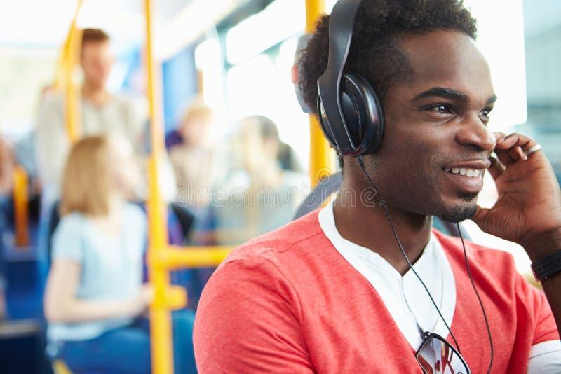 Bärande hörlurar för man som lyssnar till musik på bussresa royaltyfri foto