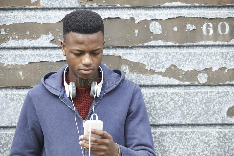 Bärande hörlurar för tonårs- pojke och lyssna till musik i Urban S arkivbilder