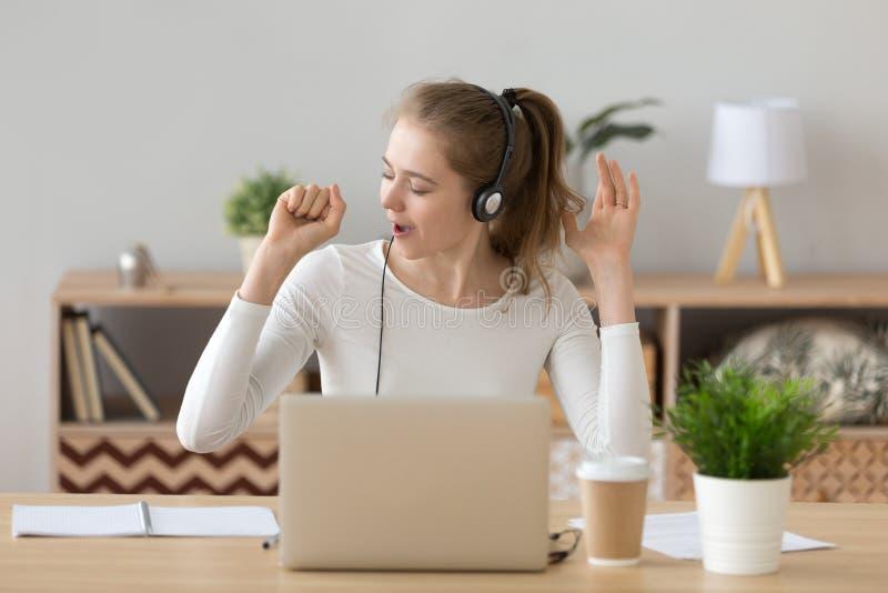 Bärande hörlurar med mikrofon för glad kvinna att tycka om musik och att sjunga arkivfoton