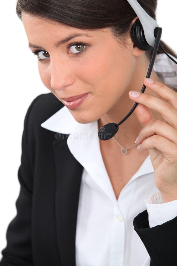 Bärande hörlurar med mikrofon för kvinna arkivbild