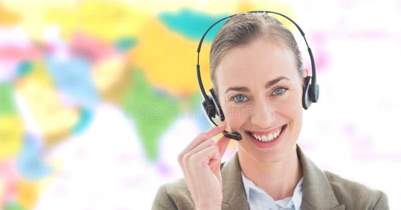Bärande hörlurar med mikrofon för resebyråmankvinna framme av världskartan royaltyfri fotografi